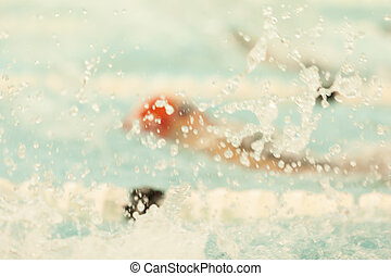A swimmer swims backstroke at a competition.