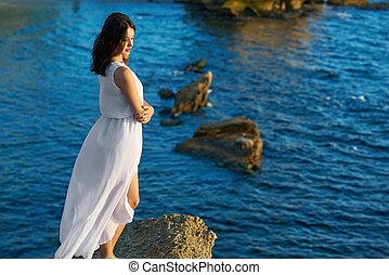 backview, di, giovane ragazza, standing, su, roccia, in, blu, estate, sea.