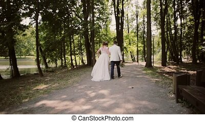 Backview of a happy couple walking on a river bank in a park holding hands on their wedding day. Beautiful white outfits