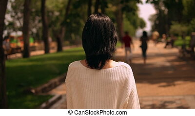 backview of a woman walking in the park
