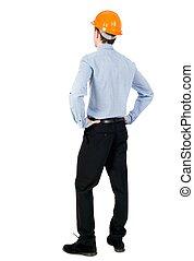 Backview of an engineer in construction helmet stands.