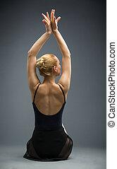 Backview of dancing on the wooden floor ballet dancer