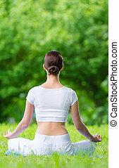 Backview of woman in asana position zen gesturing