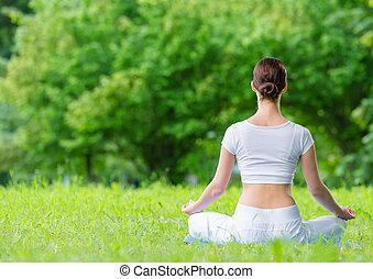Backview of woman in lotus position zen gesturing