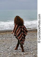 backview portrait of happy brunette woman on the beach wearing p
