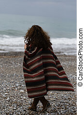 backview portrait of happy brunette woman on the beach wearing poncho