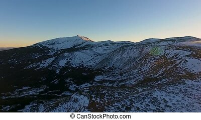 Backward aerial top view over winter snowy mountain and...