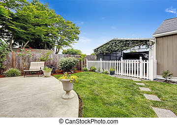 Backyard area with covered parking spot separated with white...