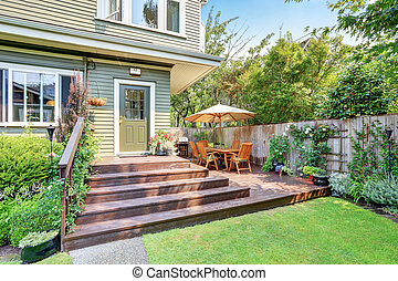 Backyard area with walkout deck, patio table set and well kept lawn. Northwest, USA