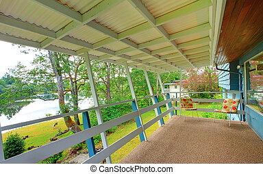 Backyard covered deck with carpet floor and water view.
