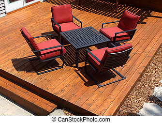 Backyard deck design with deck chairs and table.