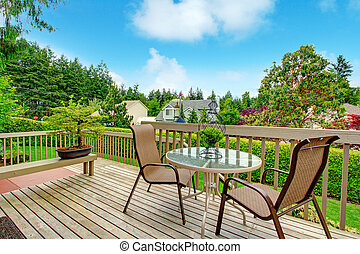 Backyard deck view. - Cozy wooden deck with glass top round...