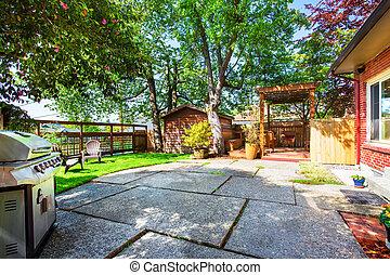 Backyard deck with pergola and concrete patio.