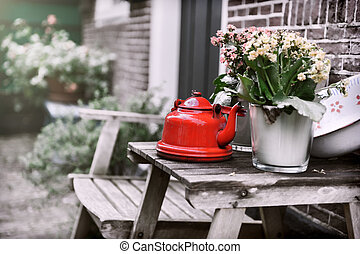 Backyard decoration with vintage kettle and flowers