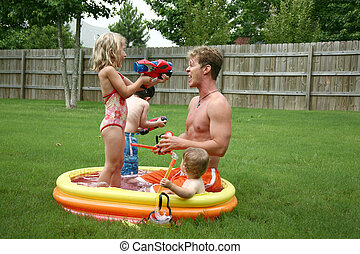 Backyard family fun in the kiddie pool. - Boys and Girl with...