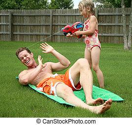 Backyard fun as girl squirts dad with watergun