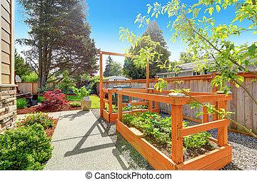 Backyard garden bed with trellis - VIew of concrete walkway...