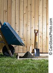Backyard, home concreting project with wheelbarrow