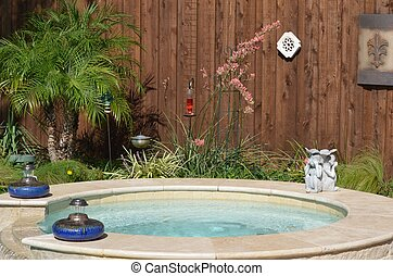 Backyard view of the hot tub with palm tree and red Texas yucca plant
