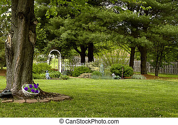 Backyard landscape with trellis and fence and large trees in early spring