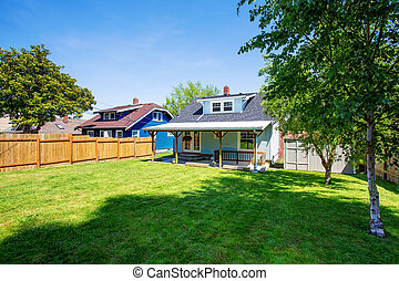 Backyard of blue American house with well kept lawn around