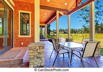 Backyard patio area - Brown and orange siding house with...