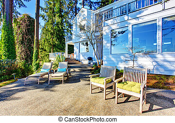 Backyard patio area with chairs, concrete walkway and landscaping desing.