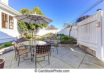 Backyard patio area with small garden