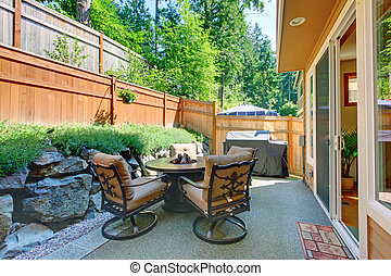 Backyard patio area with table set and concrete floor.
