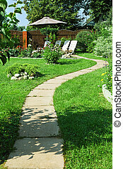 Backyard Patio - Lush blooming summer garden with paved path...