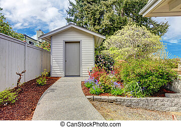 Backyard small shed and flower bed view