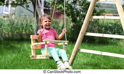 Backyard swing - Cheerful girl swinging in the background on...