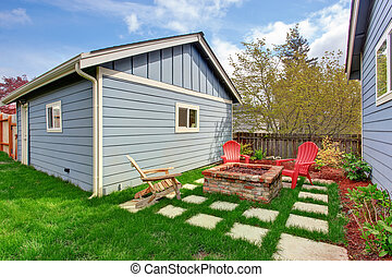 Backyard with fire pit and deck chairs - Small backyard with...