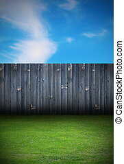 backdrop of backyard with old black wooden fence and green grass
