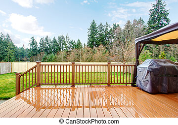 Backyard with wet deck, grill and fence during spring.