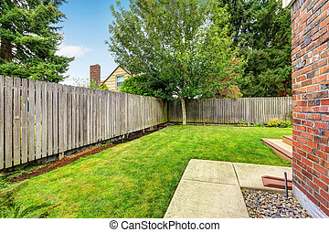 Backyard with wooden fence and walkway. Backyard with green...