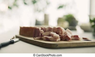 Bacon and knife on a wooden chopping board. Cooking concept.