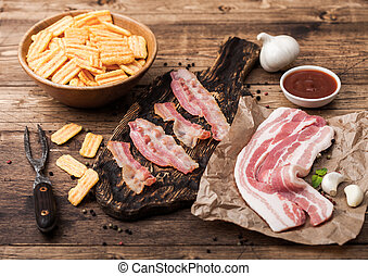 Bacon flavored snacks chips with grilled bacon rashers on vintage chopping board with smoked raw bacon on butchers paper with garlic and sauce on wooden background.