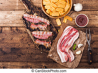 Bacon flavored snacks chips with grilled bacon rashers on vintage chopping board with smoked raw bacon on butchers paper garlic and sauce on wooden background.