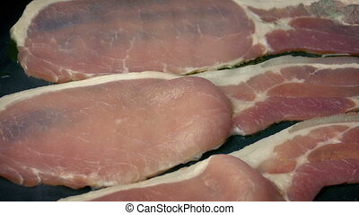 Bacon Goes From Raw To Cooked In Pan - Closeup of strips of...