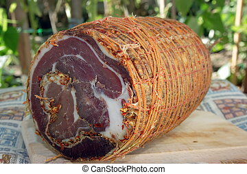 This is a typicl product of peasants living in mountains of the southern Italy (Aspromonte, high 600-700 m). A meat of pig is covered with a special set of spicies (pepperoncini calabresi) which renders the taste of final produc very spicy. Then the meat is rolled up and the cylindryc form is fixed ...