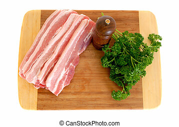 Bacon on cutting board, white background, studio shot, pepper mill, parsley on the side
