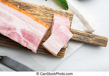 Bacon pancetta cut and sliced on white background.