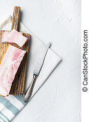 Bacon pancetta cut and sliced on white background, top view with space for text.