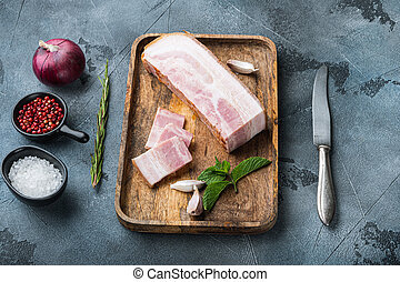 Bacon pancetta cut and sliced with herbs on grey textured background.