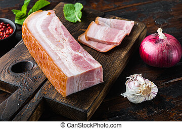 Bacon pancetta cut and sliced with herbs on wooden surface.