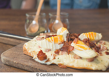 bacon pizza ontop with boiled egg