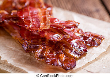 Bacon stripes (fried) with selective focus on wooden background