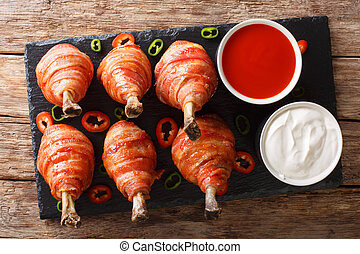 Bacon Wrapped Chicken Lollipops with sauces close-up. Horizontal top view