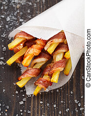 Bacon wrapped french fries in a paper cornet